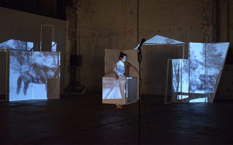 Performer Wei Zhang is walking with a set element while projection is mapped on top of that element