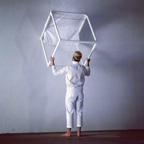 Performer Konstantinos Chaldaios is receiving a square set element from the floor above