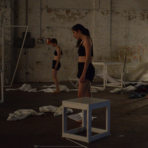 Performers Elly Rutherford and Violeta Valcheva are standing amids the ruins of the dream city