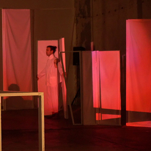 Performer Fanis Sakellariou is trapped in a set element which are projected on with images in red