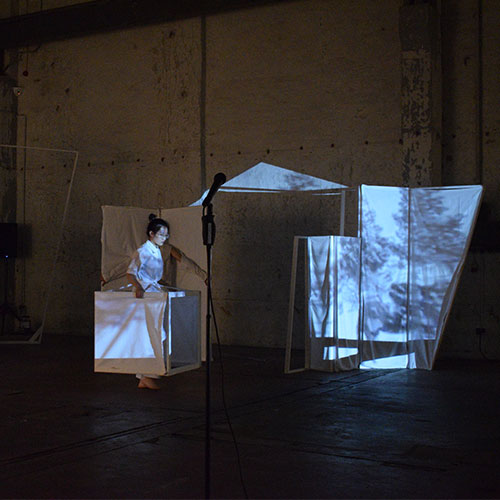 Performer Wei Zhang is walking with a set element while a projection is mapped on top of the element